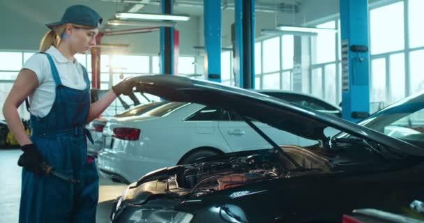 Kavkazská mladá pracovnice autoservisu přijíždí k autu, otevírá a prohledává přestávku s baterkou v motoru v garáži. Žena inženýr opravy automobilů.