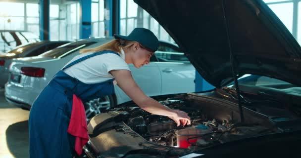 Žena Kavkazský mladý automechanik stojící v otevřeném autě a opravující motor ve velké garáži. Portrét ženy v uniformě pracující v autoopravně a vesele se usmívající na kameru uvnitř.