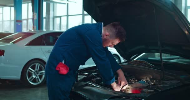 Muž Kavkazský mladý automechanik stojící u otevřeného auta a opravující motor ve velké garáži. Portrét muže v uniformě pracující v autoopravně a vesele se usmívající na kameru uvnitř.