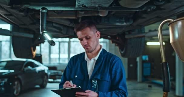 Portrét mladého bělocha, pohledného pracovníka autoservisu, jak se dívá do kamery a usmívá se se složkou a dokumentem v rukou v garáži. Muž stojící pod autem během technické kontroly.
