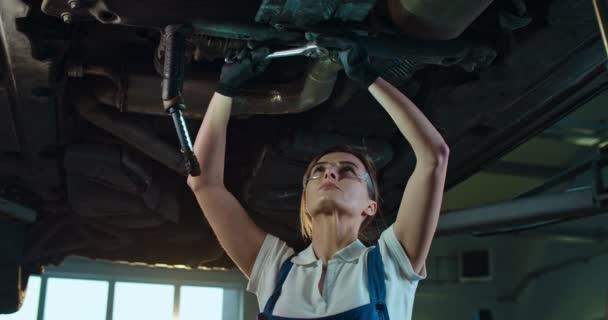 Kavkazská mladá krásná žena v uniformě a brýlích, stojící pod autem a kroutící se s klíčem v garáži. Samice mechanik pracující v servisním salonu a opravy přestávky.