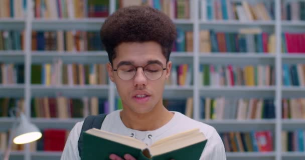 Close up of young Latino handsome guy in glasses standing and reading book in library. Good looking male student with textbook in hands studying in bibliotheca with books shelves behind. Study concept