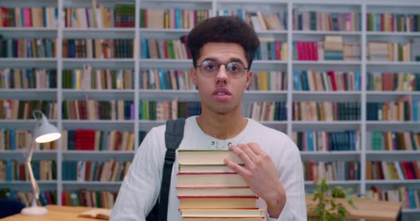 Portrait of young handsome Latino man in glasses with stack of textbooks standing in libary and looking to camera. Male student in bibliotheca with books shelves on background. Study concept.