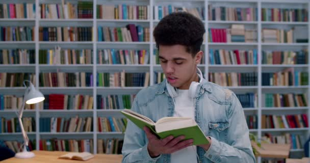 Young Latino male student reading textbook in library room and studying. Portrait of handsome guy with headphones closing book and smiling to camera in bibliotheca space.