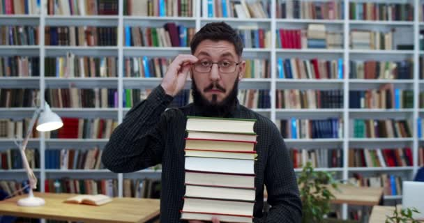 Portrait of young happy handsome Caucasian man in glasses with stack of textbooks standing in libary and laughing to camera. Male cheerful customer of book store smiling and buying many store.