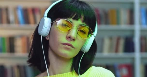 Detailní portrét drzé brunetky ve žlutých slunečních brýlích poslouchající hudbu v bílých sluchátkách a tančící vedle knihovny v knihovně s barevnými neonovými světly.