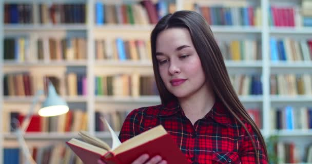 Portrait of friendly shy brunette student in checked shirt reading book and then look at camera in library.