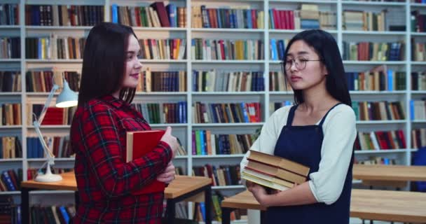 Portrait of smart young asian student in glasses speaking about school project with caucasian brunette friend in library.