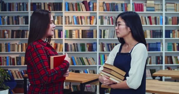 Portrait of mixed race female friends discusing exams and share their knowledge in library.