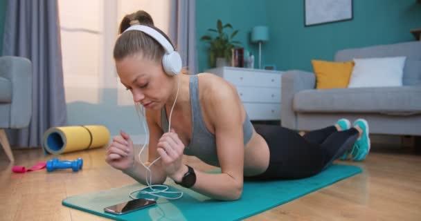 Mladá fit dívka v atletické top dělá prkno cvičení a poslouchat hudbu v bílých sluchátkách, pomocí smartphone v útulném bytě s moderním interiérem. Koncept lidí a aktivního životního stylu.