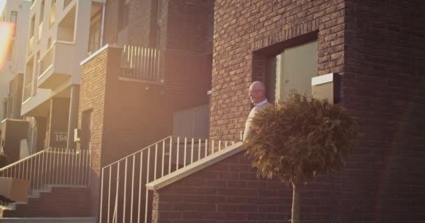 Mladá běloška přinesla krabici starému důchodci a rozdávala ji venku. Senior man getting balcel at his house outdoor from female kurýr.