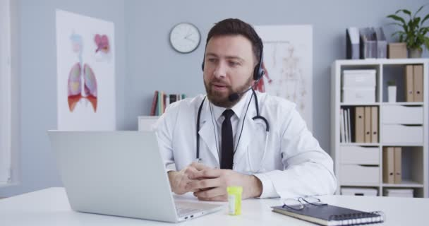 Familientherapeut im Kopfhörer sitzt am Tisch im Schrank und spricht mit dem Patienten per Webcam per Notebook. Mann führt Videochat, berät über Behandlung, ärztliche Beratung während der Quarantäne.