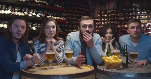 Kaukasische Freundinnen und Freunde jubeln in der Bar, wenn sie Sportspiele verfolgen. Männer und Frauen kreischen und lachen, als die Mannschaft in der Kneipe ein Tor schießt. Fußballfans schauen sich Spiel mit Bier im Fernsehen an.