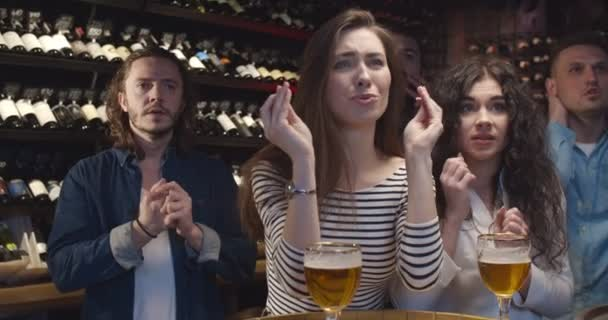 Football male and female fans watching game together in evening in pub and cheering up for their favorite team. Caucasian friends having fun and celebrating goal or victory in bar.