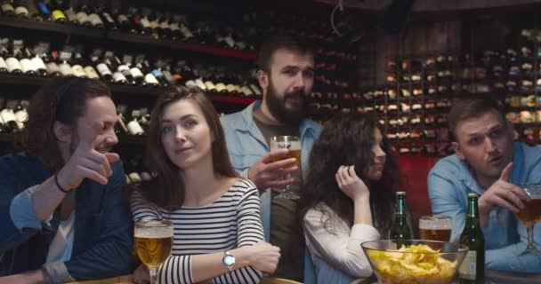 Caucasian guys and girls sitting at pub with beer in evening and watching sport channel on TV. Friends talking and discussing football game in bar. male and female cheerful fans.