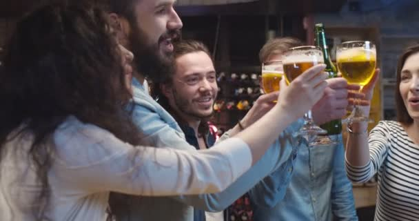 Caucasian guys and girls doing cheers gesture with beer in pub in evening and watching sport channel on TV. Friends talking and discussing football game in bar. Male and female cheerful fans.