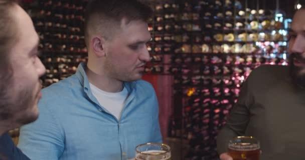 Kaukasische gutaussehende Typen, die abends in der Kneipe sitzen, Bier trinken und Sport im Fernsehen verfolgen. Freunde reden und diskutieren Fußballspiel in der Bar. Männliche Fans plaudern mit Getränken und Betreuerteam
