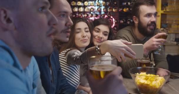 Jungs Fußballfans beobachten Spiel zusammen mit Freundinnen in der Nacht in der Kneipe und diskutieren Spiel. Kaukasische junge Männer, die in Bar über Ergebnisse sprechen. Hübsche Mädchen machen Selfie-Fotos mit dem Smartphone.