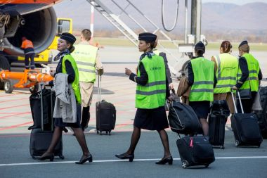 Russia, Vladivostok, 10/13/2017. Beautiful stewardesses dressed in official dark blue uniform of Aeroflot Airlines and reflective vests go to plane on airfield. Crew of plane. Aviation and transportation. stock vector