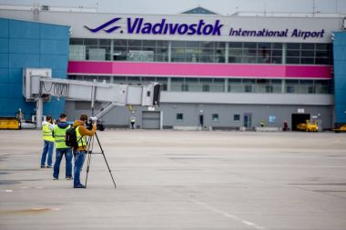 Planespotters shoot a photo in a foreground of terminal of airport of Vladivostok (VVO).
