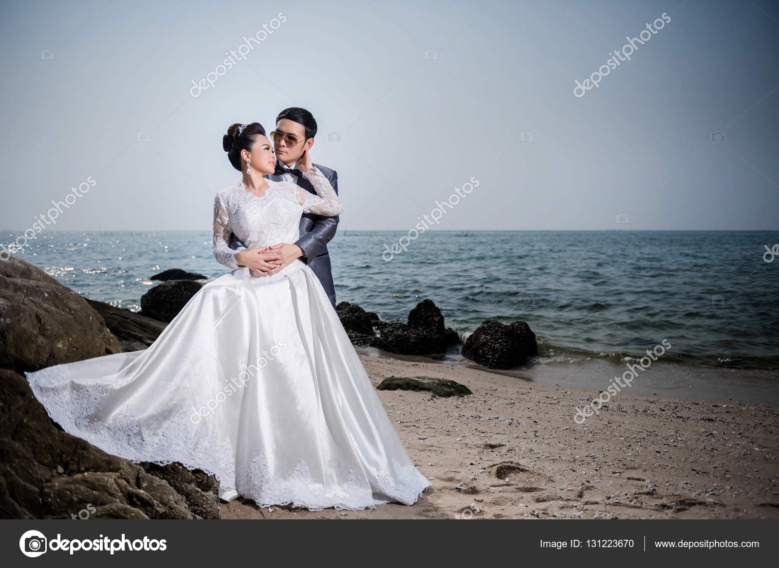 Asian couple wearing wedding dress and suit for beach wedding ce ...