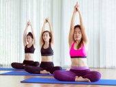 Ženy cvičení jógy představují v tělocviku fitness