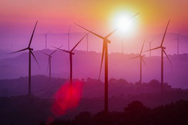 Wind turbines silhouette on mountains at sunset.