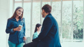 Happy businesswoman and businessman having conversation in modern office. Business corporate and community concept.