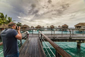 A men take photos at Sunset in a Luxury bungalow in Bora Bora