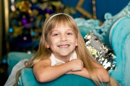 Photo pour Smilling girl se trouve sur un canapé bleu sur le fond d'un sapin de Noël - image libre de droit
