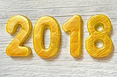 Happy New Year 2018. Golden numbers on white wooden background.