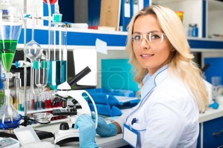 Foto de Joven mujer atractiva científica en gafas protectoras y guantes investigando en el laboratorio químico científico - Imagen libre de derechos