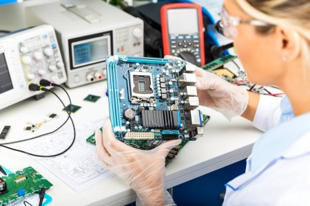 Photo for Young female digital electronic engineer examining computer PC motherboard in laboratory - Royalty Free Image