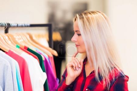 Foto de Joven rubia sonriente atractiva mujer con el pelo largo de compras en la tienda de ropa de moda desgaste y la elección de la ropa - Imagen libre de derechos