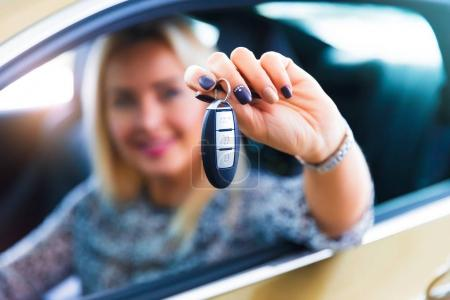 Photo for Happy young woman driver holding auto keys in her new modern luxury car - Royalty Free Image