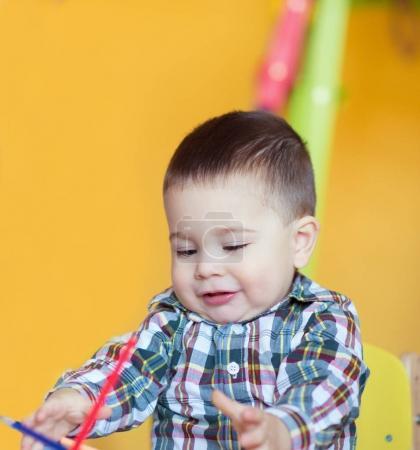 Photo pour Mignon petit bébé garçon dessin aux crayons colorés à la table - image libre de droit