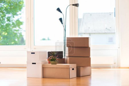 Photo for Many cardboard boxes in big bright  house during relocation - Royalty Free Image