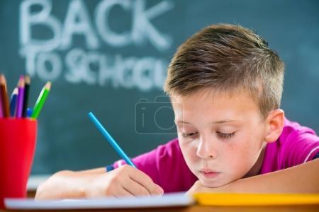 Photo pour Écolier mignon étudient au tableau noir de la salle de classe au premier plan - image libre de droit