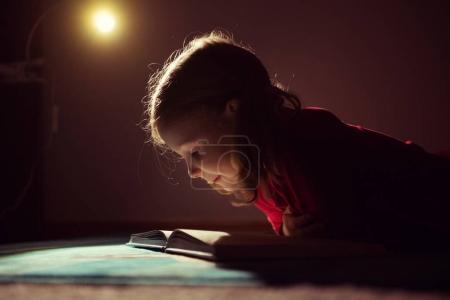 Photo pour Jolie petite fille lisant le livre dans sa cachette sous le lit avec une lampe de poche à l'obscurité - image libre de droit