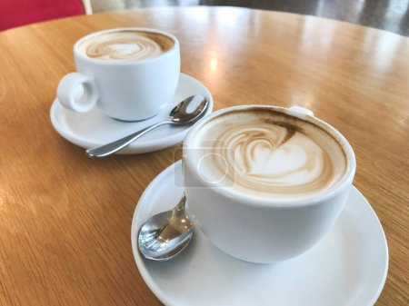 Photo for Two cups of flat white coffee on wooden table at cafe - Royalty Free Image