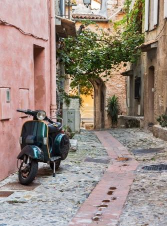 Old motor scooter on a narrow street