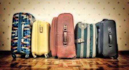 Row of used suitcases on parquet floor