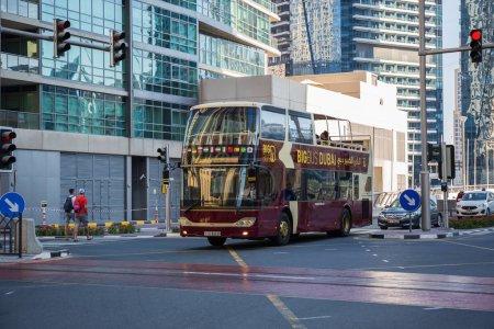 DUBAI, UAE - NOVEMBER 29, 2017: Travel bus on urban street of Dubai Marina.