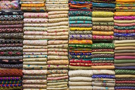 Stack of cloth with authentic arabian patterns on shelf in store