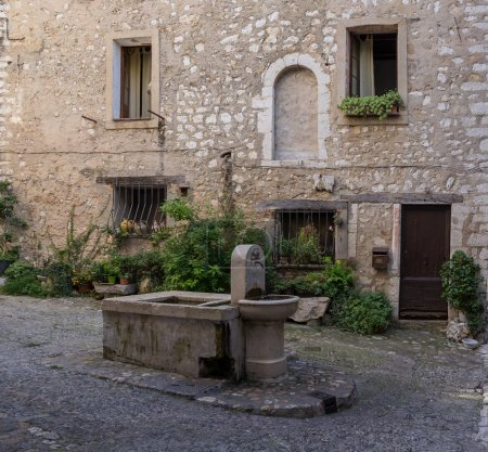Closeup of drinking fountain in square in medieval French village.