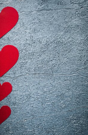 Composition of red paper hearts on metallic background Valentine