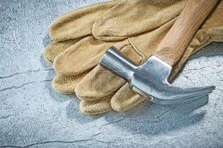 Leather safety gloves claw hammer on metallic background constru