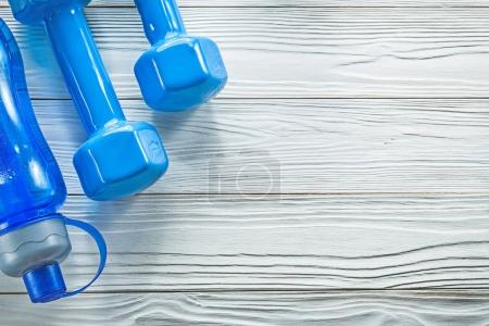 Water bottle blue dumbbells on wood board sports training concep
