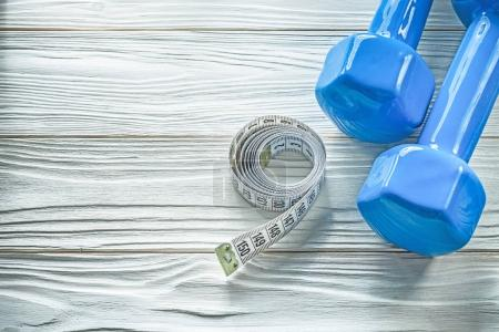 Dumbbells rolled tape measure on wooden board fitness concept