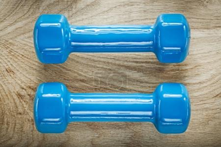 Blue dumbbell weights on wooden board sports training concept